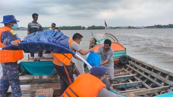 Kasat Intelkam Polres Tanjab Barat AKP Hermanto Menyerahkan Paket Sembako pada Salah Satu Nelayan yang Baru Pulang Melaut, Jumat (10/9/21). FOTO : SatIntelkam