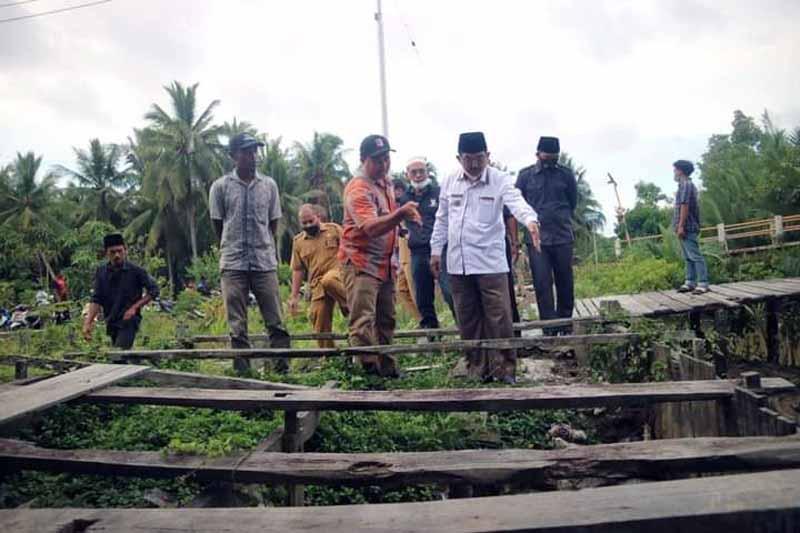FOTO : Bupati Anwar Sadat Saat Meninjau Langsung Tanggul atau Pintu Air di Parit Gantung, Desa Tungkal I, Kecamatan Tungkal Ilir, Senin (29/03/21).