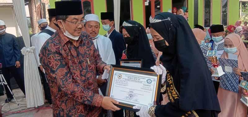 FOTO : Bupati Tanjab Barat, KH. Anwar Sadat dan Istri Hj. Fadhilah Saat Menyerahkan Piagam Kepada Wisudawan Santri Khotmil Qur'an.