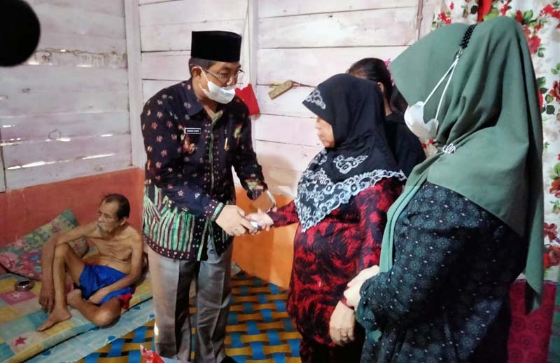 FOTO : Bupati Kabupaten Tanjung Jabung Barat, H. Anwar Sadat, menyambangi salah satu keluarga Disabilitas, bapak Anwar dan ibu Hhalijah di Desa Teluk Pengkah, Kecamatan Tungkal Ulu, Kamis (11/03/21).