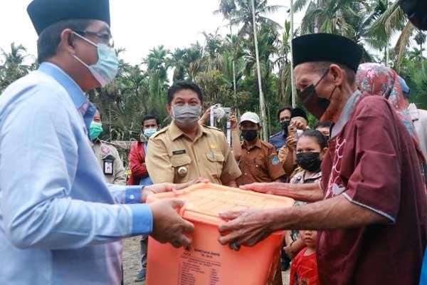 Bupati H. Anwar Sadat menyerahkan bantuan sosial Pemerintah Kabupaten Tanjab Barat kepada Siar Pani (70) yang mengalami musibah kebakaran di Parit Cegat, Selasa (11/05/21). FOTO : Prokopim.