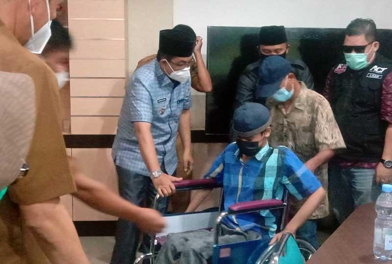 FOTO : Bupati Tanjab Barat H. Anwar Sadat menyerahkan bantuan kursi roda kepada Azwir anak penyandang disabilitas atas nama Azwir di desa Teluk Pengkah, Kecamatan Tebing Tinggi, Selasa (23/3/21).