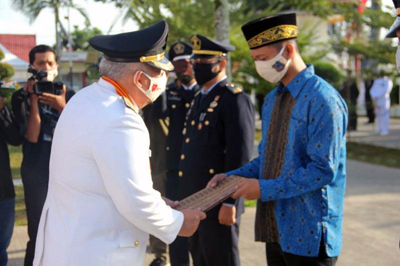 FOTO : Bupati Tanjab Barat Dr. H. Safrial Secara Simbolis Menyerahkan SK Remisi Kepada Perwalikan Napi Seusai Upacara Peringatan Detik-Detik Proklamasi di Hamalam Kantor Bupati, Senin (17/08/20).