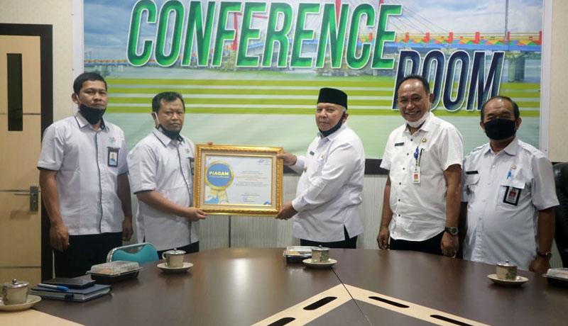 FOTO : Kepala Badan Pusat Statistik Tanjung Jabung Barat Wasi Riyanto, S.ST, M.E MenyerahkanPenghargaan kepada Bupati Tanjab Barat Dr. H. Safrial di Ruang Rapat Bupati, Rabu (19/08/20).