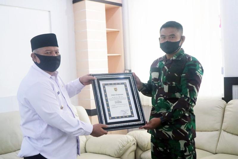 FOTO : Bupati Tanjab Barat Dr. H. Safrial saat Menerima Penghargaan dari Pangdam II Sriwijaya Diserahkan Dandim 0419/Tanjab Kolonel Inf Erwan Susanto, S.IP di ruang rapat Bupati Tanjabbar, Rabu (19/08/20).