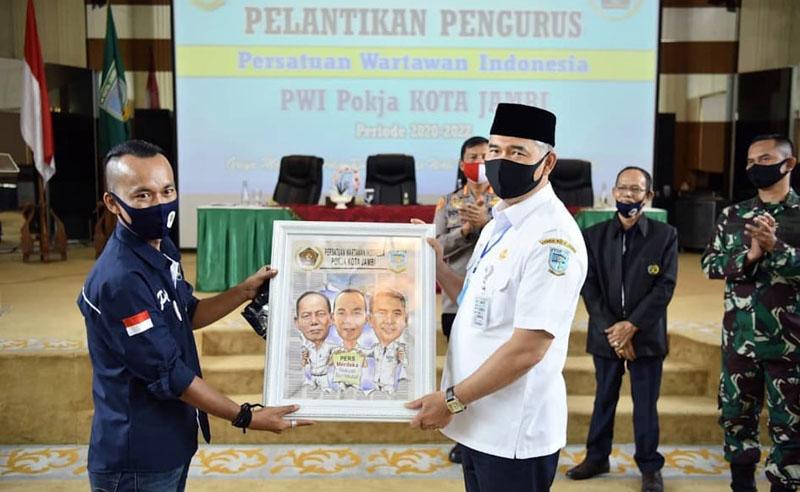 FOTO : Walikota Jambi Dr. H. Syarif Fasha Menyerahkan Cinderamata Pada Acara Pelantikan Kelompok Kerja (Pokja) Persatuan Wartawan Indonesia (PWI) Kota Jambi Periode 2020-2023 di Aula Griya Mayang, Rabu (07/07/20).