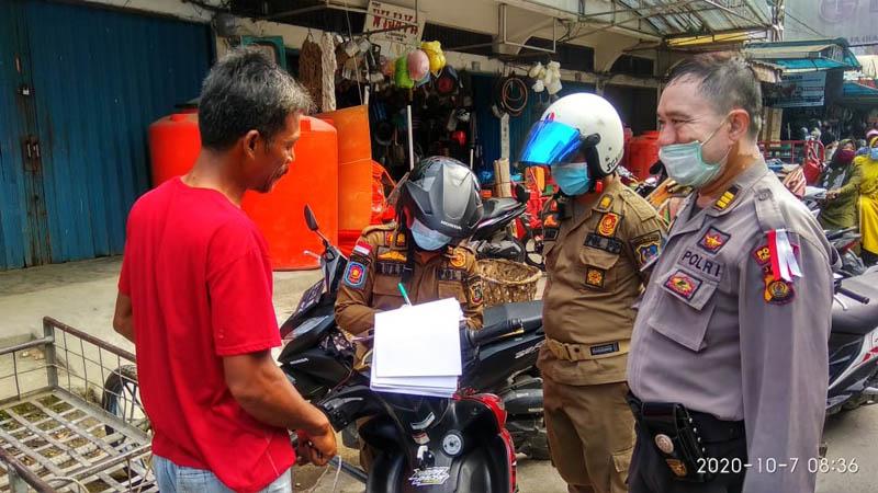 FOTO : Petugas Satpol PP Mendata Warag yang Tak Memakai Masker saat Satgas Covid-19 menggelar sosialisasi protokol kesehatan penggunaan masker berkeliling di jalan dan tempat di Kota Kuala Tungkal, Rabu (07/10/20).