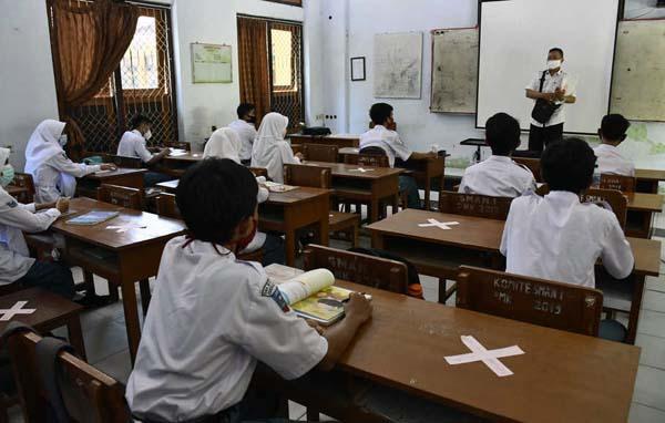 Guru memberikan materi pelajaran saat uji coba pembelajaran tatap muka di SMAN 1 Pamekasan, Jawa Timur, Rabu (19/8/2020). Pembelajaran tatap muka di tengah Pandemi COVID-19 tersebut, per kelas dibagi menjadi dua kelompok yang dilaksanakan bergantian setiap minggunya. ANTARA FOTO/Saiful Bahri/aww.