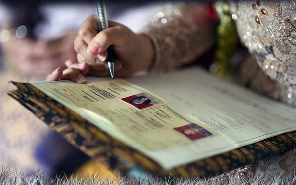 Ilsutrasi : Pasangan Menikah Menandatangani Buku Nikah.