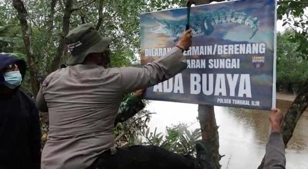 Anggota Polsek Tungkal Ilir danBabinsa Memasang Spanduk Imbau Warga Tak Mandi dan Bermain di Bantaran Sungai Bram Itam, Minggu (11/07/21).