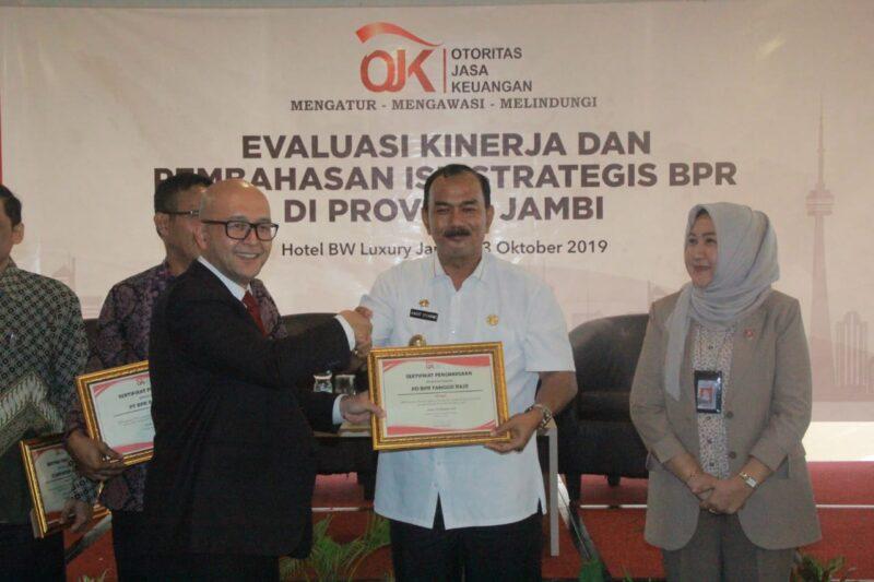 FOTO : Kepala OJK Jambi Endang Nuryadin Menyerahkan Piagam Penghargasn Kepada Wakil Bupati Tanjung Jabung Barat Drs. H. Amir Sakib di Hotel BW Luxury Jambi, Rabu (23/10/19)