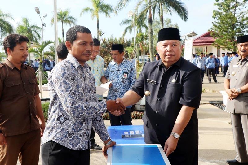 FOTO : Bupati Tanjung Jabung Barat Dr. H. Safrial Menyerahkan Bantuan Kepada Perwakilan Pedangan Yang Menrima Usai Upacar Gabungan TNI, Polri, dan Aparatur Sipil Negara (ASN) di Halaman Kantor Bupati, Selasa (17/03/20)
