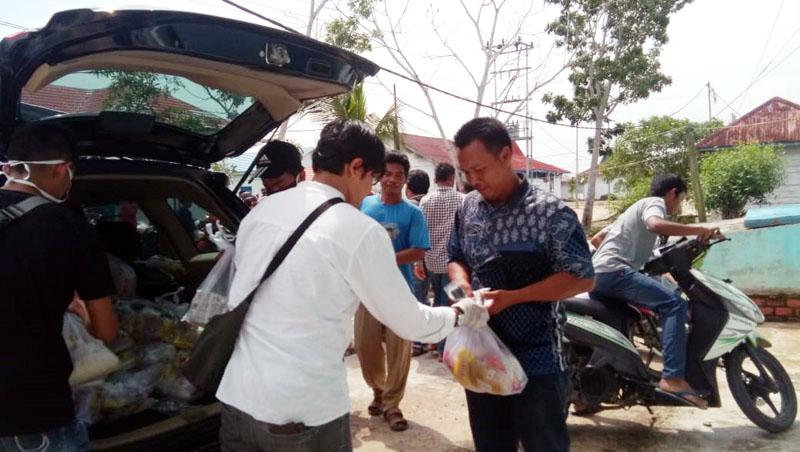 FOTO : Ketua HNSI Kabupaten Tanjung Jabung Barat Syuprayogi Syaiful, S.IP saat Melakukan Pembagian Sembako Kepada para Nelayan di Pelabuhan TPI Kuala Tungkal, Sabtu (04/04/20).