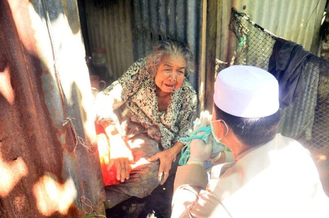 FOTO : Kapolres Tanjab Barat AKBP Guntur Saputro Saat Menyambagi Salah Satu Warga Ketika Baksos Pembagian Sembako bersama BRI Unit Kuala Tungkal, Selasa (21/04/20).