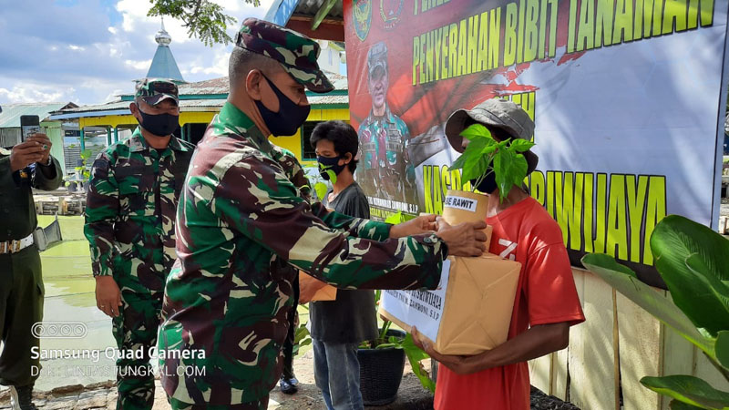 FOTO : Kasdam II/ Sriwijaya Brigjen TNI Mohammad Zamroni, S.IP Saat Menyerahkan Bibit Tanaman dan Tali Asih di Depan Komplek Asrama Kodim 0419, Sabtu (30/05/20).