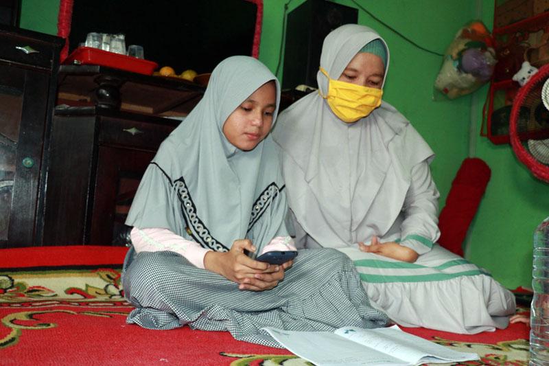 FOTO : Kasih Aprilia Gunawan (kiri), siswi SDN 03/V Kuala Tungkal belajar dari rumah bersama orang tuanya. Selama PJJ, Kasih mendapatkan pembelajaran berkualitas dari gurunya lengkap dengan laporannya.