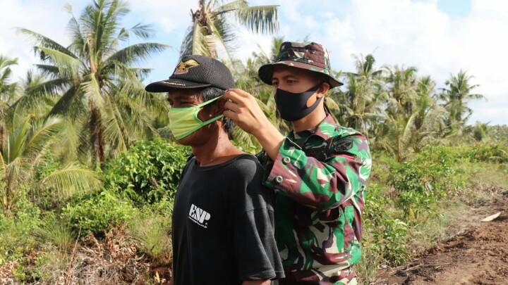 FOTO : Satgas TMMD 108 Kodim 0419/Tanjab saat Memasangkan Masker ke Warga