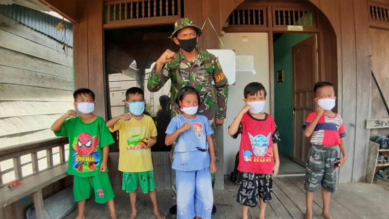 FOTO : Satgas TMMD 108 Kodim 0419/Tanjab saat Memasangkan Masker ke pada Anak-Anak di Desa Labuan Pering.