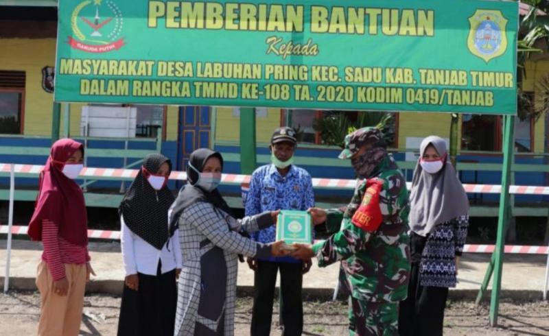 FOTO : Satgas TMMD membatu membagikan 20 buah Al Qur'an Juz Amma untuk anak-anak, Desa Labuhan Pering, Rabu (22/07/20).