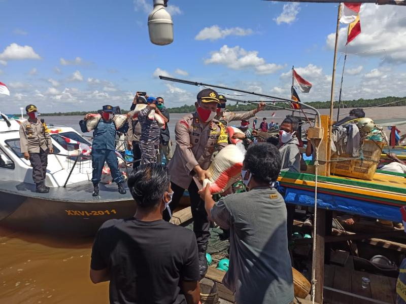 FOTO : Kapolres Tanjabbar AKBP Guntur Saputo Menyerahkan Bantuan Beras Kapolri kepada para Nelayan di perairan Sungai Pengabuan, Kuala Tungkal, Senin (17/08/20)