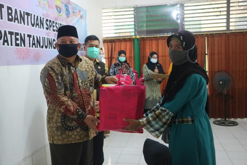 FOTO : Bupati Tanjab Barat H. Safrial Saat Menyerahkan Bantuan Spesifik Perempuan dan Anak dari Kementrian P3A di Aula Kantor Dinas P3AP2KB, Kamis (01/10/20).