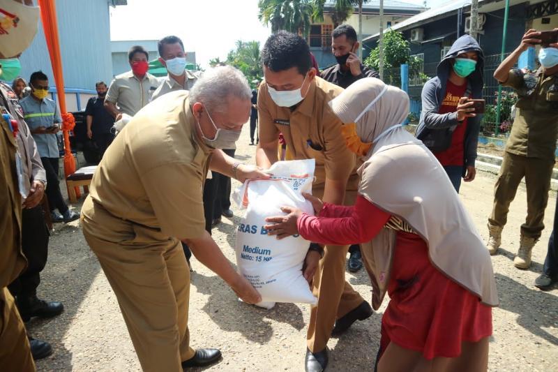 FOTO : Bupati H. Safrial Saat Serahkan Secara Eimbolis BSB Tahun 2020 kepada Perwakilan Keluarga PKH di Gudang Bulog Kuala Tungkal, Selasa (20/10/20).