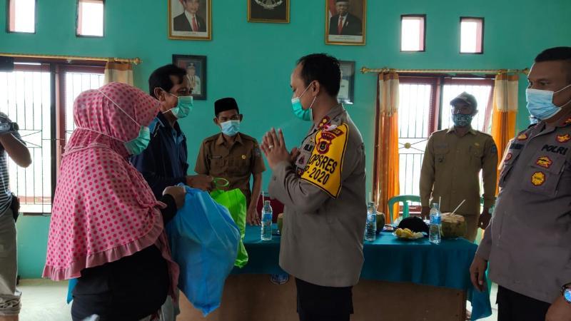 FOTO : Kapolres Tanjabbar AKBP Guntur Saputro, SIK, MH Saat Menyerakhkan Paket Sembako dan Masker pada salah satu Warga, Selasa (03/11/20).