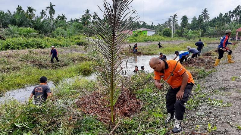 FOTO : Jumat Bersih Polsek Pengabuan bersama perangkat Desa Karya Maju dan warga Membersihkan Embung Air, Jumat (26/02/21).