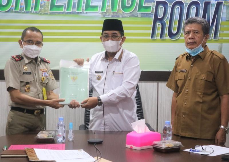 FOTO : Bupati Tanjab Barat KH. Anwar Sadat Saat Menerima Pemyerahan 35 Sertifikat Tanah Milik Pemkab dari Kepala BPN Supriadi di ruang rapat Bupati, Senin (29/03/21).