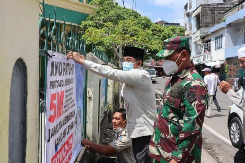 Bupati Tanjab Barat H. Anwar Sadat Ketika Memasang Baleho Himbauan Prokes di Masjid Raya Kuala Tungkal, Senin (10/05/21). FOTO : Prokopim