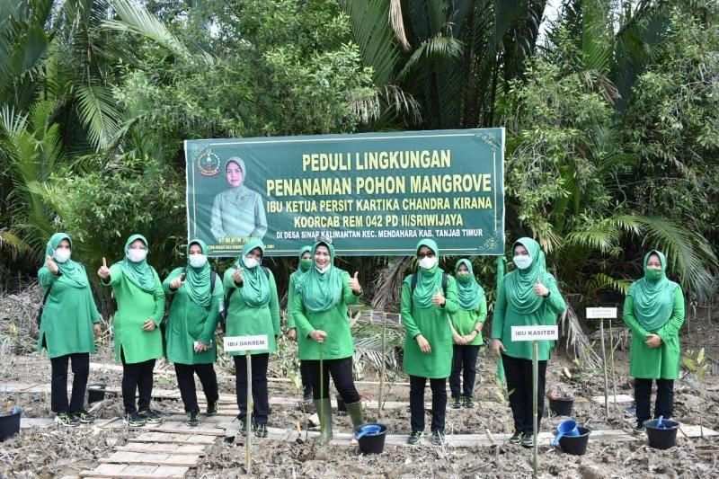 Ketua Persit Kartika Chandra Kirana Koorcab Rem 042 PD II/Sriwijaya Ny. Dewi Zulkifli melakukan penanaman Mangrove di Fesa Sinar Kalimantan, Kecamatan Mendahara, Jum'at (18/06/21). FOTO : Korem042.
