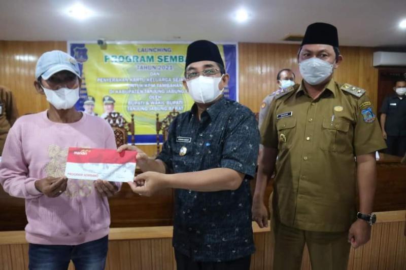 Bupati Tanjab Barat H. Anwar Sadat Saat Menyerahkan KKS Peneeima Program Sembako BNPT Tahun 2021, Selasa (13/07/21). FOTO : PROKOPIM