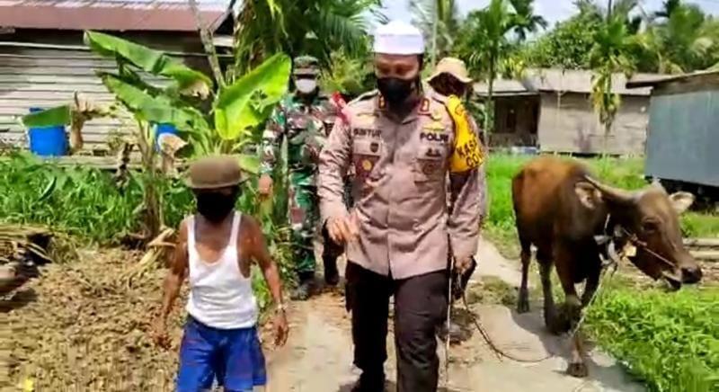 Kapolres Tanjab Barat AKBP Guntur Saputro, SIK, MH saat Mengantar Hewan Kurban Seekor Sapi ke Kampung Melayu Parit 10 Sungai Saren. FOTO : HUMASRES