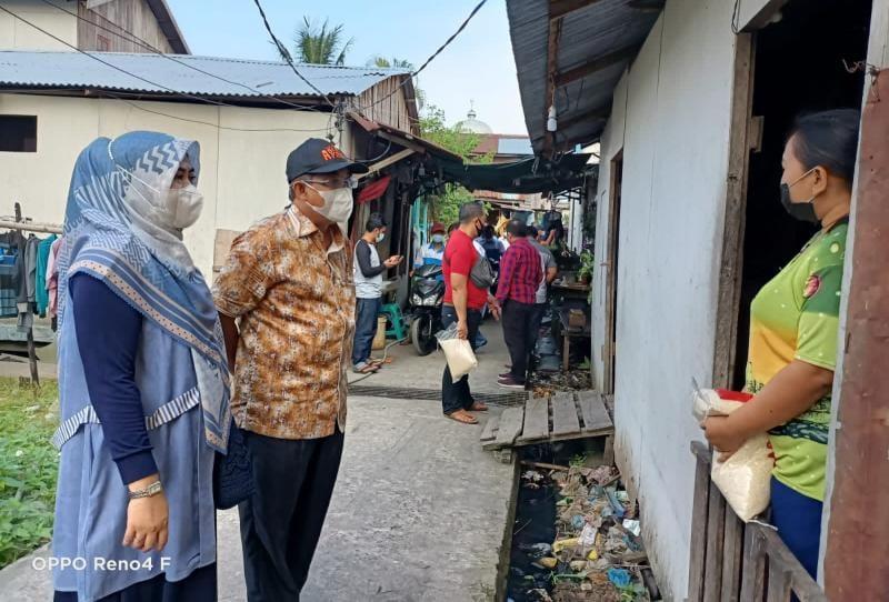 Bupati H. Anwar Sadat dan Istri Umi Fadhilah Sadat saat Memberikan Sembako ke warga, Minggu (08/8/21). FOTO : ISTIMEWA.