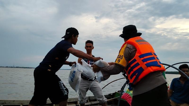 Aski Kapolres Tanjabbar, AKBP Guntur Saputro Menyerahkan Bansos Beras bantuan dari Kapolda Jambi kepada Nelayan di Pompong, Minggu (08/08/21). FOTO : HUMASRES