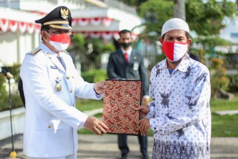 Bupati Tanjab Barat H. Anwar Sadat Menyerahkan SK Remisi kepada perwakilan warga binaan Lapas kelas II B Kuala Tungkal seusai Upacara HUT RI di Halaman Kantor Bupati, Selasa pagi (17/08/21). FOTO : PROKPOIM.
