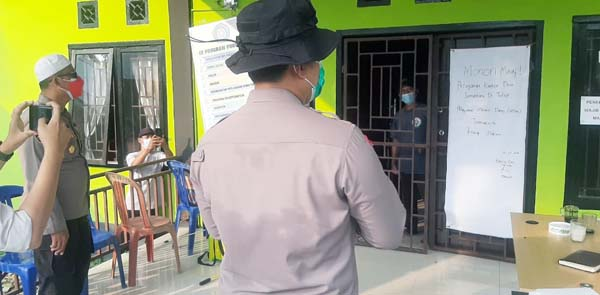 FOTO : Kapolres Tanjab Barat AKBP Guntur Saputro, SIK, MH Saat Dialog Jarak jauh dengan Salah Satu Pasien yang menjalani Isolasi di Kantor Desa Jati Emas, Kecamatan Bram Itam, Kamis (10/06/21). FOTO : Humas ResTjb