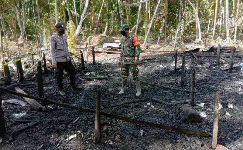 FOTO : Petugas Melakukan Pemeriksaan di Rumah warga di RT 05 Dusun Tanjung Baru Desa Sungai Jering, Kec. Pengabuan, Kabupaten Tanjab Barat yang hangus terbakar, Kamis (25/02/21).