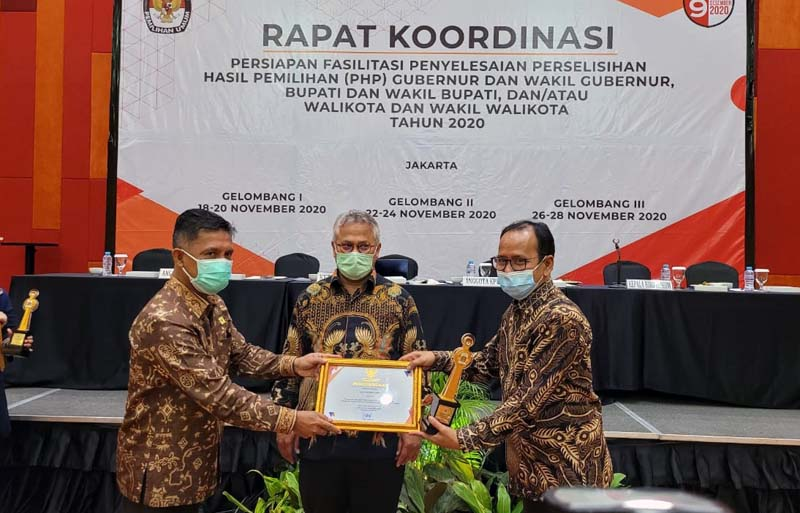 Ketua KPU RI Arif Budiman Menyerahkan Penghargaan JDIH kepada Ketua KPU Provinsi Jambi H. M. Subhan di Hotel Grand Mercure Jakarta, Kamis (26/11/20).