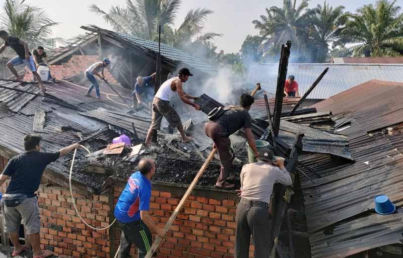 Petugas gabungan Warga Melakukan Upaya Pemadaman secara Manual di Jln. Raden Usman RT 02 Kec. Merlung. FOTO : Istimewa