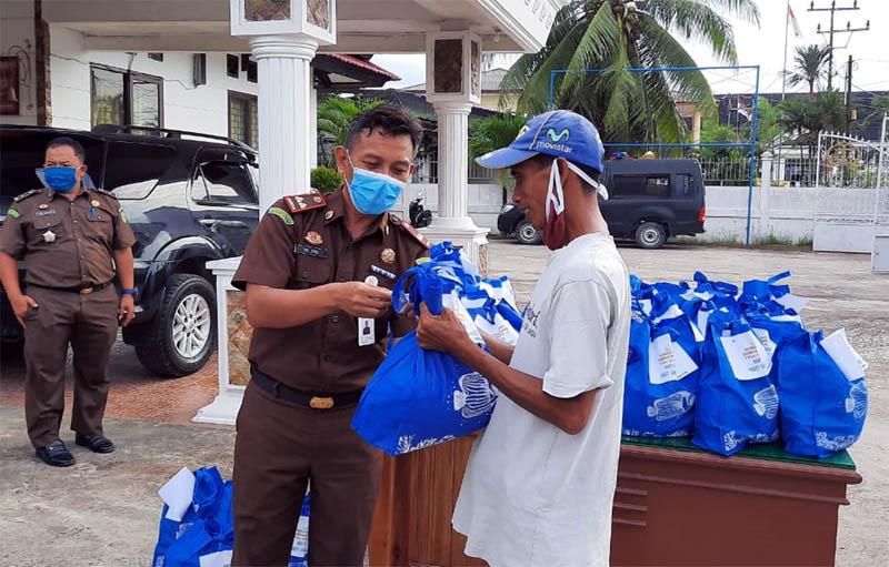 FOTO : Kejari Tanjab Barat Tri Joko, SH saat Menyerahkan Bantuan Sembako Kepada Salah Satu Abang Becak di Kuala Tungkal, Selasa (05/05/20)