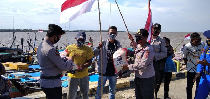 FOTO : Kapolsek KSKP IPTU Agung Heru Wibowo, SH, MH Menyerahkan Bendera Kepada Para Nelayan, Sabtu (15/08/20)