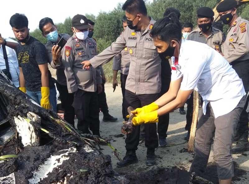 Anggota Polres Tanjab Timur Saat Memeriksa Bangkai Mobil dan Melihat Tulang Diduga Manusia di TKP Penemuan, Rabu (03/03/21). FOTO : Gt