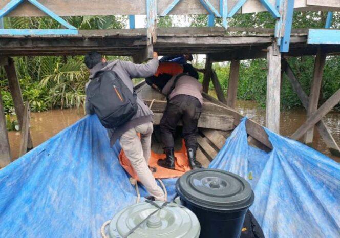 FOTO : Petugas Logistik Menunduk Melewati Kolong Jembatan yang Hampir Sangkut oleh Perahu Pompong di Salah Satu Desa di Kecamatan Pengabuan, Selasa (08/12/20).