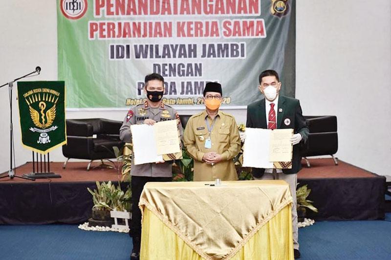 FOTO : Gubernur Jambi H. Fachrori Umar Menyaksikan Penandatanganan Kerjasama oleh Ketua IDI Wilayah Jambi Dr. dr. H. Deri Mulyadi dan Kepolda Jambi Irjen Pol Firman Shantyabudi di Hotel Shang Ratu, Selasa (21/07/20).