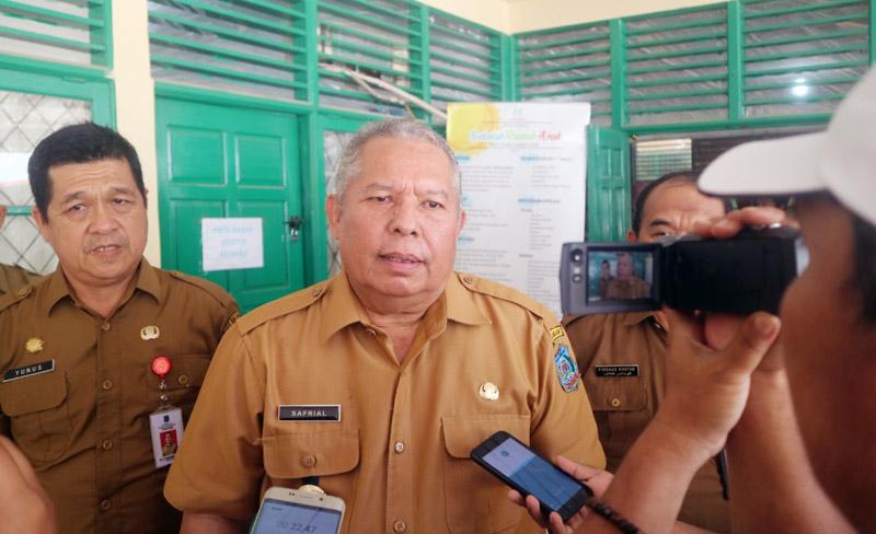 FOTO : Bupati Tanjab Barat Dr. Safrial Diwawaincarai Wartawan Usai Membuka Rapat Koordinasi Gugus Tugas KLA di Dinas P3AP2KB, Selasa (10/03/20).