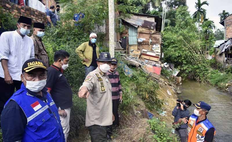 FOTO : Wali Kota Jambi Dr. H. Syarif Fasha Saat Meninjau lokasi rumah warga yang longsor di sempadan Sungai Kenali Besar (saluran primer anak Sungai Batanghari) akibat abrasi (29/01/21).