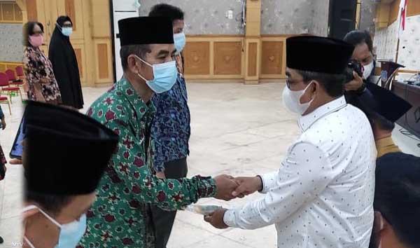FOTO : Bupati Tanjab Barat H. Anwar Sadat Menyerahkan SK Pensiun kepada Sekretaris BKPSDM H. Muhammad Salim yang masuk Masa Purna Bhakti PNS Tahun 2021 di Gedung Balai Pertemuan Kantor Bupati, Senin (31/05/21).