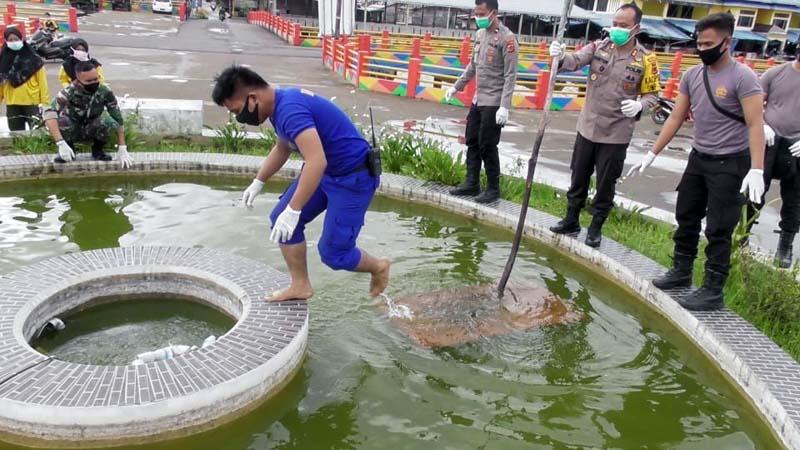 FOTO : Kapolres AKBP Guntur Saputro Meminpin Karya Bakti jumat bersih membersihkan taman air mancur di objek wisata WFC Kota Kuala Tungkal, Jumat (18/12/20).