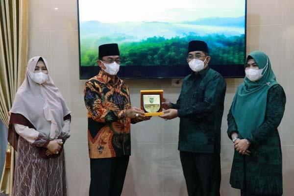 FOTO : Bupati Tanjung Jabung barat, H. Anwar Sadat Menerima Palakat Kenang-kenangan dari Bupati Indragiri Hilir (Inhil), H. M. Wardan, Senin (24/05/21).